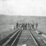 A group of men working on the tracks west of the St. Mary's station.  They are looking at an large bull snake stretched out on the tracks – 1905.  Courtesy Galt Museum & Archives - 19760234013