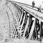 View of one of the wooden trestle bridges along the Crowsnest Branch.  Two railway workers and a velocipede is visible – 1898.  Courtesy Galt Museum & Archives - 19780259009