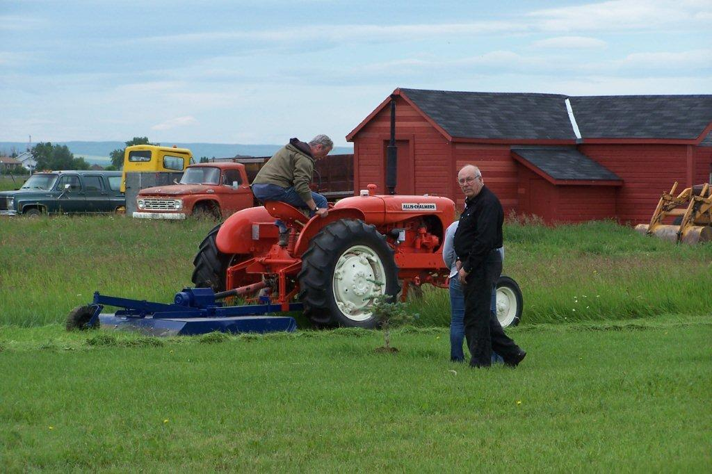 c97-100_5094.jpg - Earl Stamm tries out the just restored tractor and rotary cutter, Lanny Aitkens observes his picture being taken, offers to give autograph! June 2012 - Bill Hillen Photo